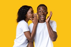 African-american woman sharing secret or whispering gossips into her boyfriend's ear, yellow studio background. Black lady whispering words of love to her amazed man who screaming and gesturing