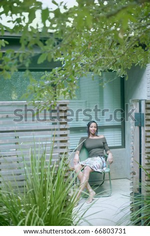 African American woman sitting in chair next to house