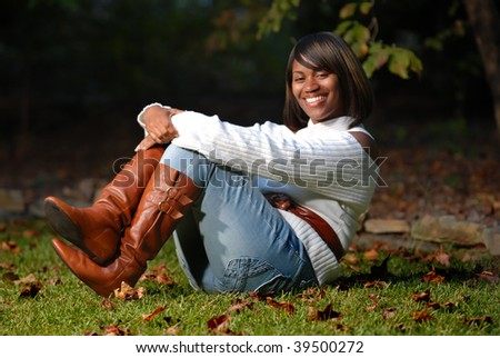 African -American woman sitting on grass smiling