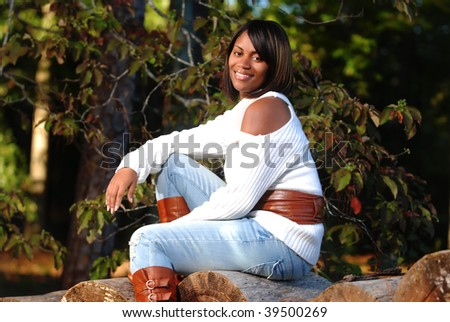 African-American woman sitting on log smiling