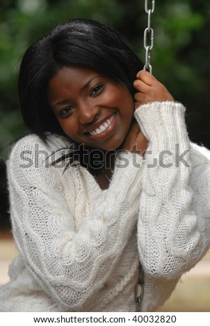 African-American woman smiles while sitting in a swing