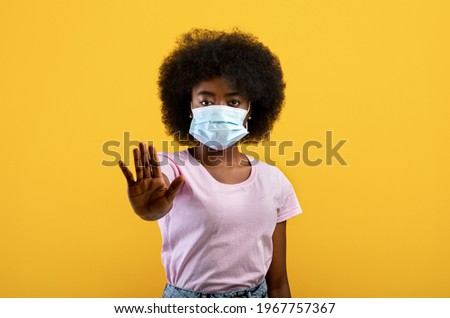 African american woman suffering from sick, wearing mask and comply with social distance, standing on yellow background, studio shot. Black lady in protective mask, fenced off with hand Stock photo ©