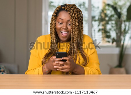 African american woman using smartphone scared in shock with a surprise face, afraid and excited with fear expression