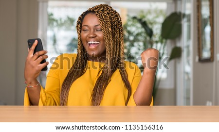 African american woman using smartphone screaming proud and celebrating victory and success very excited, cheering emotion