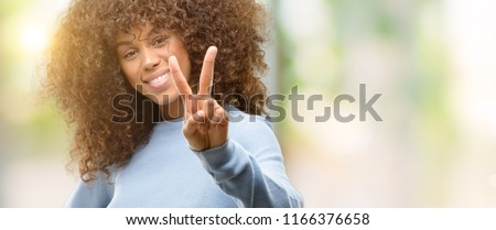 African american woman wearing a sweater smiling looking to the camera showing fingers doing victory sign. Number two.