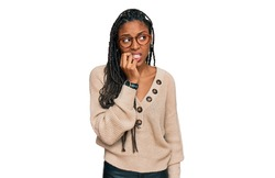 African american woman wearing casual clothes looking stressed and nervous with hands on mouth biting nails. anxiety problem.