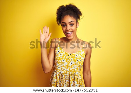 African american woman wearing casual floral dress standing over isolated yellow background Waiving saying hello happy and smiling, friendly welcome gesture