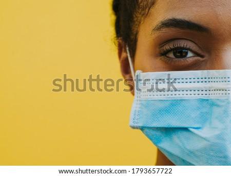 African american woman wearing medical mask against corona virus Foto stock ©