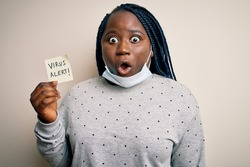 African american woman wearing medical mask holding reminder with virus alert message scared in shock with a surprise face, afraid and excited with fear expression