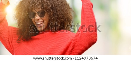 African american woman wearing sunglasses happy and excited celebrating victory expressing big success, power, energy and positive emotions. Celebrates new job joyful #1124973674