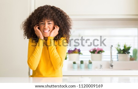 African american woman wearing yellow sweater at kitchen covering ears with fingers with annoyed expression for the noise of loud music. Deaf concept.