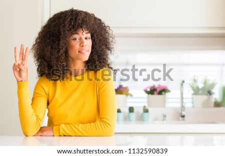 African american woman wearing yellow sweater at kitchen showing and pointing up with fingers number three while smiling confident and happy.