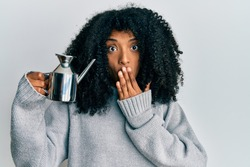 African american woman with afro hair holding olive oil bottle covering mouth with hand, shocked and afraid for mistake. surprised expression