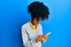 African american woman with afro hair using smartphone typing message angry and mad screaming frustrated and furious, shouting with anger. rage and aggressive concept.