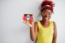 African american woman with afro hair, wear yellow singlet and eyeglasses, hold Antigua and Barbuda flag isolated on white background.
