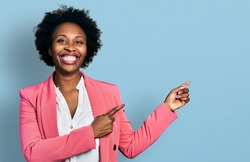 African american woman with afro hair wearing business jacket smiling and looking at the camera pointing with two hands and fingers to the side.