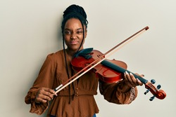 African american woman with braided hair playing violin skeptic and nervous, frowning upset because of problem. negative person.