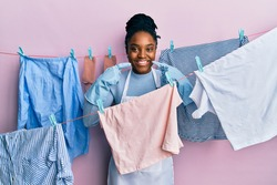 African american woman with braided hair washing clothes at clothesline smiling cheerful showing and pointing with fingers teeth and mouth. dental health concept.