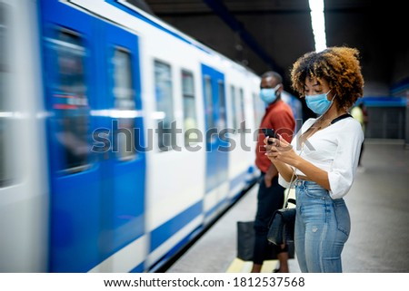 African American woman with face mask using smart phone waiting for the train on platform. stock photo