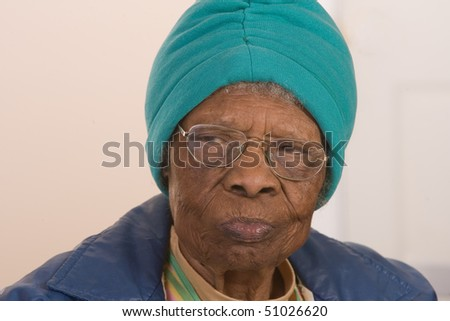 African American woman with glasses looking to the side.