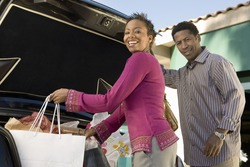 African American woman with man loading shopping bags in car