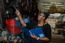 African american worker woman wear spectacles crossed arms holding clipboard standing in factory auto parts. female employee business warehouse motor vehicle.