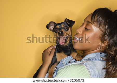 African American young adult female holding Miniature Pinscher dog.