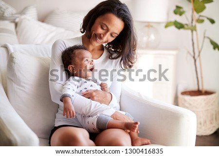 African American young adult mother sitting in an armchair in her bedroom, holding her three month old baby son in her arms and looking down at him smiling, close up