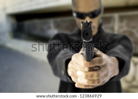 african american young black male, urban setting, very shallow depth of field, focus on barrel, armed scary man