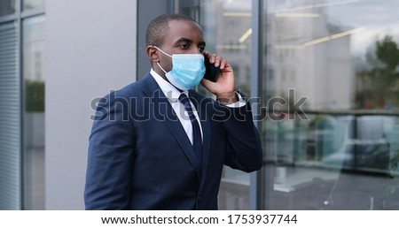 African American young businessman in medical mask walking the street and talking on mobile phone. Male pedestrian in respiratory protection strolling outdoor and speaking on cellphone. Conversation.