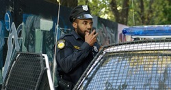 African American young cop in hat and uniform working at patrolling. Policeman standing at his police car and speaking in walkie-talkie. Cop talking in ratio.