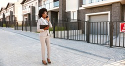 African American young female real-estate agent standing at street at suborb neighborhood and talking on mobile phone. Businesswoman with documents looking for house and speaking on cellphone.