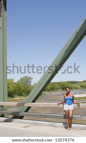 African American young female standing near a bridge with a bright blue sky behind