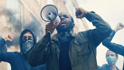 African American young handsome guy with scarf on face protesting in middle of crowd of protesters and screaming mottos in megaphone. Guy leading at manifestation and riot for human rights in smoke.