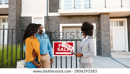 African American young happy married couple in medical masks standing outdoor at new house with female real-estate agent smiling to camera. Sold home. Pandemic concept. Buying dwelling.