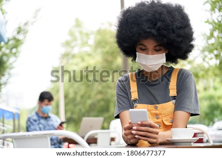 African American young hipster gen z female with Afro hair wearing face mask holding smart phone using mobile apps sitting at table in outdoor cafe. Social distancing everyday life and tech concept Stock photo ©
