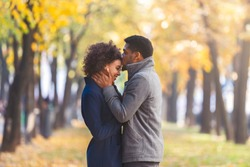 African american young man kissing his girlfriend forehead while walking in autumn city park, copy space