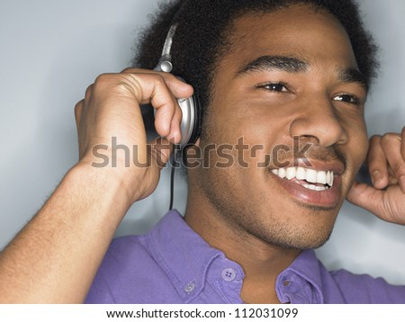 African American young man listening music through headphones - stock photo