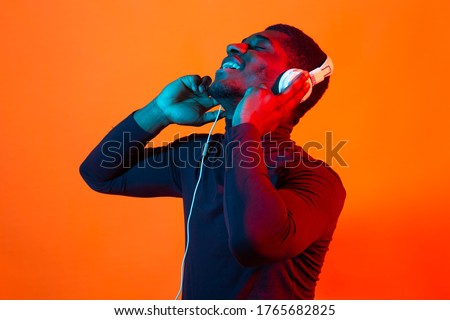 African american young man listening to music online dancing and singing with headphones, neon light. Music and technology concept.
