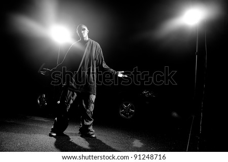 African American young man wearing baggy clothing posing under dramatic lighting with lens flare.