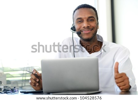 African American young operator with headset and laptop at workplace showing thumb up