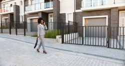 African American young stylish beautiful female real-estate agent walking the street at suborb neighborhood and talking on mobile phone. Businesswoman speaking on cellphone outdoor at outskirt.