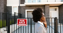 African American young stylish female real-estate agent at suburb street and talking on mobile phone. Businesswoman looking for house and speaking on cellphone. Dwelling for sale.