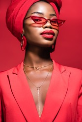 african american young woman in stylish outfit, sunglasses and turban isolated on red