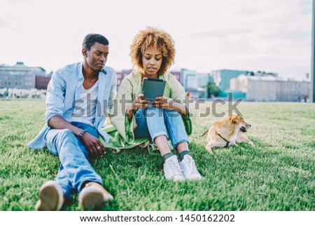 African american young woman with curly hair updating application on modern touch pad device sitting together with dark skinned boyfriend on green grass in park with dog enjoying sunny day