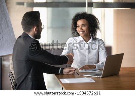 African and arab businesspeople seated at desk in boardroom shaking hands express respect, starting business negotiations, client and representative consultation, job interview human resources concept