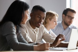African and asian different age colleagues seated at desk in co-working room look at laptop screen discuss new corporate app, more experienced mate explain program software to intern mentoring concept