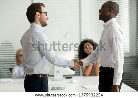 African and caucasian employees standing in shared office handshaking, executive manager and client greeting at each other shake hands express regard. Concept of praising, first impression, new worker #1375932254