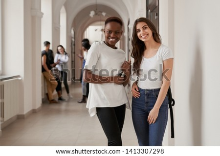 African and Caucasian girls standing on corridor of university and smiling. Women keeping friends, studying in international university together and resting on break.