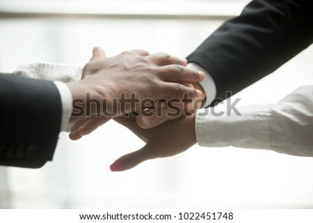 African and caucasian partners join hands in pile together, motivated multiracial business team promising help and support, engagement or unity in collaboration, commitment in teamwork, close up view